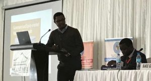 Shakim is at a podium speaking at a conference